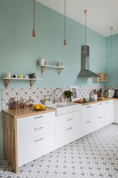 Pretty kitchen! Patterned tile, white cabinets, butcher block counter, mint walls