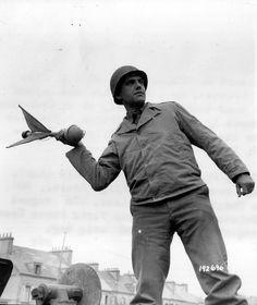 https://flic.kr/p/dsMcyF | p000979 | Un  soldat américain simule le  lancement d'une grenade Panzerwurfmine voir ici: en.wikipedia.org/wiki/Panzerwurfmine version colorisée: www.flickr.com/photos/mlq/3577340409/ Selon ce site : recherche.archives.manche.fr/?id=recherche_documents_figures Cote:13 Num 981  S/Sgt Howard D. Tourneir, of 4224 S. Miro St, New Orleans, La., holds the new german antitank hand. Throwing rocket at an ordnance supply depot in Cherbourg. 6/08/44 Il s'agiit du S/Sgt…