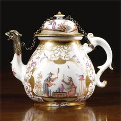 A Meissen tea pot and cover circa 1725 each side painted with a chinoiserie scene depicting two figures in the manner of J.G.Höroldt, the cover attached to the handle and spout with a gilt-metal chain, replacement gilt-metal animal head terminal