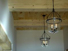 """Oversized smoke bell lanterns illuminate the hallway. """"They had the right mass for the hallway,"""" explains interior designer Linda Woodrum. """"The perfect feel against the rough wood."""""""
