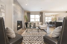Make your fireplace the focal point of your living room by accenting it with a full height tile surround,<br></a>as seen in this Jayman MasterBUILT Allure showhome in Secord, Edmonton. A patterned rug in similar<br/>tones accents the surround, making this living area an energetic center to your whole house. Plank Walls, Living Area, Living Rooms, Neutral Colors, Oversized Mirror, Family Room, Rugs, House, Furniture