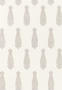 Katara Paisley Wallpaper. This traditional wallcovering features a classic elongated paisley motif, which is derived from an antique wood block pattern. Katara Paisley is block printed with delicate, lace-like detail in a openly spaced, half drop repeat pattern, in colorations that range from porcelain blues on white to exotic plum and antique metallic gold on a craft paper tan ground.