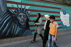 An Iranian family walks past anti-US graffiti on the wall of the former US embassy in Tehran on July 14, 2015.