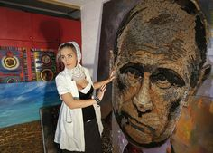 "Ukrainian artist Dariya Marchenko works on a portrait of Russian President Vladimir Putin named ""The Face of War,"" which is made of 5,000 cartridges brought from the front line in eastern Ukraine, in Kiev on July 23, 2015."