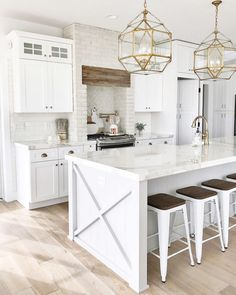 white kitchen design with natural wood floors and gold pendant lights