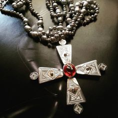 Hand crafted sterling silver cross with diffusion orange sapphire, the cross has been engraved by a Tuareg craftsman, with freshwater pearls, worn long or short $300