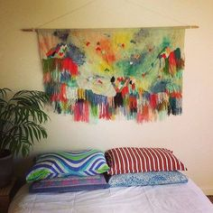 Here's how to decorate a bed without spending a lot:  buy colorful, unmatched pillowcases from a thrift store; hang a colorful textile using a Command Hook.