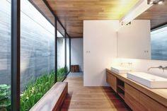 The master bathroom is warmed by use of organic golden hued wood on floor, ceiling and cabinetry.