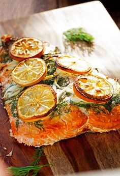 Fresh fillet of salmon covered in lemon, onions and dill and then barbecued on soaked maple planks that infuse the salmon with beautiful smoky flavor and protect from overcooking.  Juicy, tender and flavorful salmon every time!  #planksalmon #compoundbutter