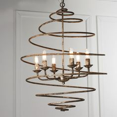 Antique Gold Spiral Spring Chandelier - 6 light This elegant swirling chandelier is poetry in motion for your room. The unique spiraling spring shaped body encircles a more traditional six arm mini chandelier putting a modern spin on classic design. A mottled, aged gold finish adds rustic refinement for a new twist on traditional decor