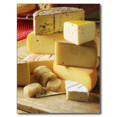 Stack of various cheese on chopping board postcard