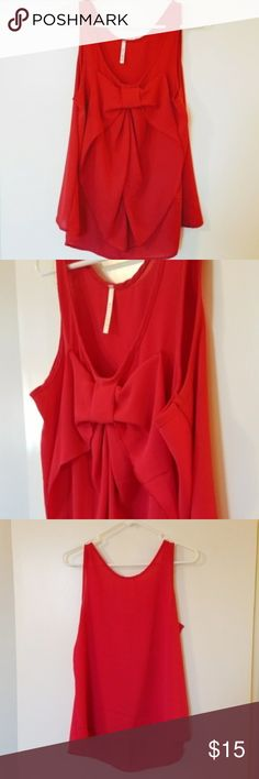 """Red Christmas bow loose tank top M Red Christmas bow loose tank top M. Loose fitting and flowy. Excellent condition never worn. It's a bright red orange color. Mezzanine brand. 36"""" chest, 23.75"""" long. 100% polyester. Looks great with an A line skirt for a Christmas party! Mezzanine Tops Tank Tops"""