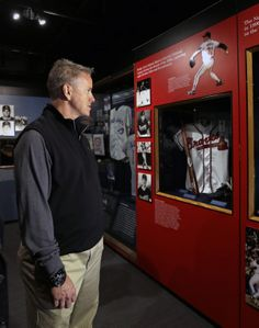 Former Atlanta Braves pitcher Tom Glavine looks at a Braves exhibit during his orientation visit at the Baseball Hall of Fame on Monday, March 17, 2014, in Cooperstown, N.Y. Glavine will be inducted to the hall in July. (AP Photo/Mike Groll)