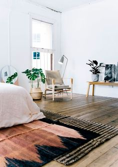 Modern bohemian bedroom with Scandinavian furniture and printed, layered rugs