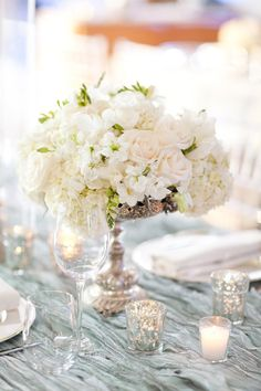 low centerpiece. pretty linen. mercury glass candle holders.
