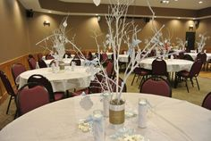 Baptism centerpieces, candles wrapped in yarn, cans with painted branches and crosses and baptism verses hanging from tree