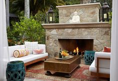 With a dominating fireplace and lush  surroundings, this patio is the perfect spot for outdoor entertaining. Blue  garden stools provide extra seating; white sheer drapery and candlelight create  an intimate setting.