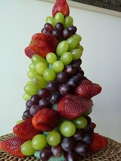 Easy fruit topiary. Great edible centerpiece for a party! Use toothpicks and skewer fruit into a foam shape.