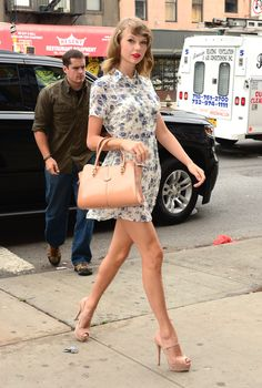 Our Favorite Look of the Day   Twist Thursday, July 10: Taylor Swift looked so stylish rocking a pretty floral dress while walking around New York City. She matched her light tan handbag to her nude heels in a totally chic way – those platform shoes make her legs look miles long! She even polished off her hair with a cute flower barrette, which we totally want to copy.