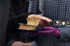 U.S. President Barack Obama places his hand on two bibles, held by first lady Michelle Obama, as he recites the oath of office during swearing-in ceremonies in Washington. By Brooks Kraft