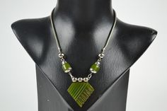 This 1930s vintage Art Deco necklace features a large carved green Bakelite pendant with chrome and Bakelite beads
