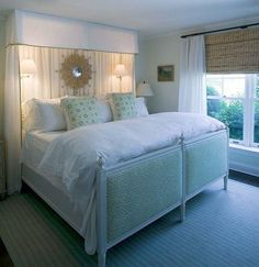 white & green bedroom design with striped green rug, bamboo roman shades, white sheers, upholstered green bed, green pillows, sconces, sunburst mirror, white cornice box and white drapes with green ribbon trim.