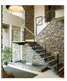 open staircase against stone wall with black metal railings