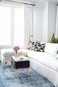zdesign at home summer home tour blue vintage inspired rug white slip covered couch white walls white linen drapes black fur stool black and white pillows leather pillow-1