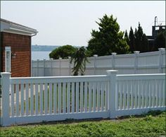 Vinyl Capped Sudbury Fence - This elegant fence with a special kickboard defines the home's front yard, while a complementing 6 feet high version creates privacy along the side. While the fence has the look and feel of natural wood, it is in fact crafted with low maintenance cellular vinyl.