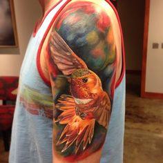 Absolutely breathtaking realistic hummingbird in flight tattoo by Chris Hess