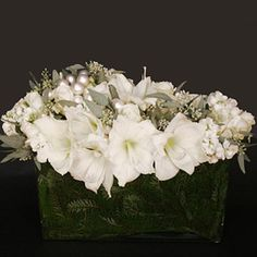 Brides Magazine: White Winter Wedding Flower Ideas  --This white ice arrangement is filled with white amaryllis, seeded eucalyptus, roses and white ornament balls and sits in a modern vase filled with fragrant cedar for a seasonal touch. Ovando, ovandony.com.    Photo: Courtesy of Ovando