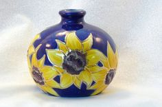 Whats more stunning than a brightly colored ring of sunflowers on a cobalt blue background?    This weed pot vase is just the little pick me