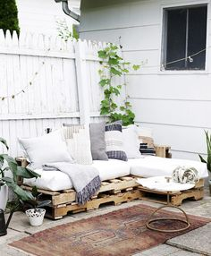 Pallet Outdoor Furniture Wood pallet couch on patio with white cushions and throw pillows. - This article will show you the steps, materials and tools you need to create an L-shaped couch using pallet wood and how to make no sew cushions. Wood Pallet Couch, Pallet Patio Furniture, Outdoor Furniture Plans, Pallet Benches, Pallet Tables, Pallet Bar, 1001 Pallets, Recycled Pallets, Pallet Ideas