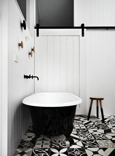 The article is about patterned tiles but I love the whole look of this bathroom.  Classic black and white - 2-tone bath (LOVE!), white walls, black tap wear, the TILES and sliding barn door