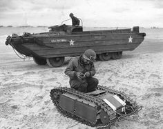 A U.S. soldier inspects the German self-propelled mine 'Goliath' (Sd.Kfz. 302). This modification of the mine 'Goliath E-Motor', equipped with two motors Caterpillar. Sector landing 'Utah' in Normandy. Behind American amphibious vehicle DUKW.