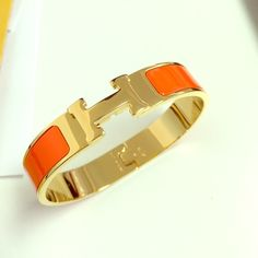 "Orange Enamel H Style Bangle Bracelet Yellow Gold BRAND NEW !!! TOP quality Orange Enamel Bracelet H Style. Yellow Gold Finish. COMES WITH AN ORANGE H POUCH. 1:1 compare to the original brand. Bracelet material will not tarnish or turn color. MEASUREMENT: 7.25"" all around approximately. Feel free to make an offer. I also do bundle discount for purchase of 3 items or more in my closet. Thanks  xoxo Jewelry Bracelets"