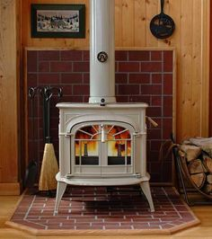 A wood burning stove often sits on a hearth pad. This pad must be fire resistant and able to withstand the weight of the stove. The hearth pad can be as simple as a metal shield or even a concrete slab, but the stove must sit on a non-combustible surface. Hearth Pad, Brick Hearth, Wood Stove Parts, Vermont Castings Wood Stove, Wood Stove Surround, Real Estate Staging, Pellet Stove, Stove Fireplace, Fireplace Ideas