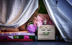 Detalle de una sala de juegos debajo de una escalera, con un tejido colgado a modo de «puerta» y una caja llena de juguetes.