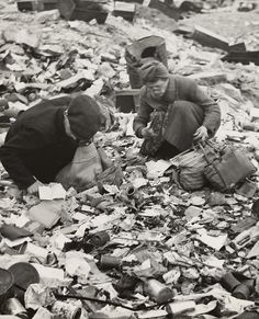 World War II, two Germans searching for food in a garbage dump, original caption 'Hunger, the price of defeat', Berlin, Germany, photograph by Emil Reynolds, 1945.