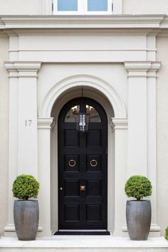 A Brilliant London Style Door in high gloss black in stark contrast to the white classical edifice.