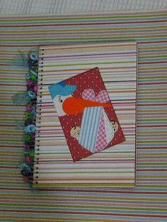 Um lindo caderno, decorado e encadernado com folhas de scrapbook, com espaço para fotos, com carimbos e tags adicionados