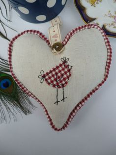 hanging heart stuffed with dried lavender. main fabric is Laura Ashley linen and a sweet little bird/hen motif appliqued and embroidered onto the front using red check cotton. The heart has checked piping round the outside and a ribbon and vintage button handstitched in place. measures 16cm by 16cm at the widest points and has a total length of 18cm when hanging.