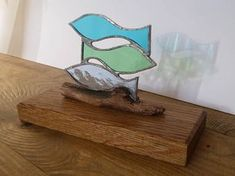 This is a handmade shoal of fish made from stained glass mounted on a wooden base. It would make a lovely gift, or a beautiful addition to your own home! The fish have been soldered using the traditional copper foil method, they have then been mounted on a piece of driftwood I found