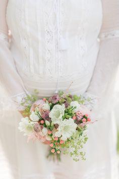 Une femme enceinte porte un bouquet de fleurs roses et blanches
