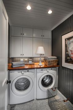 This spacious laundry room boasts a side-by-side, front loading washer and dryer tucked underneath a butcher block countertop. Crisp white cabinets provide plenty of storage for detergents and cleaning supplies.
