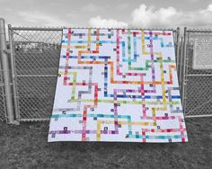 """This scrap-busting quilt is made with 1,600 fabric squares and 25 unique blocks. Use scraps in 12 colors to create the subway """"lines"""" and """"stops"""" on this stylized transit map. Each of the four size variations follows the same layout using a different size of fabric squares. All sizes include instructions for a pieced back. There are two different ways to use colorful fabric scraps in this quilt:SUPER SCRAPPY VERSIONThis version is..."""