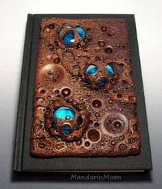 https://flic.kr/p/noK1en | Lunar Landscape journal | This is a custom journal cover I made from polymer clay and glass gems. Lots of texture here! It reminds me of the surface of the moon...if the moon was made of chocolate. Hmm, what a wonderful idea! Much better than cheese. :)
