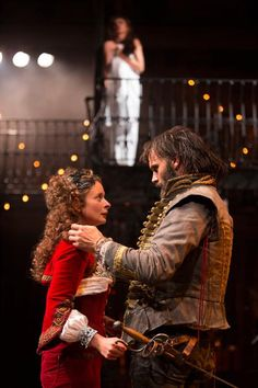 A bearded man studies the face of a beautiful woman in red - The Rover at the RSC Swan Theatre, Stratford upon Avon