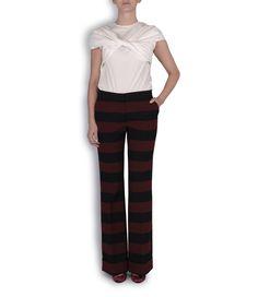 Pantalones de rayas berenjena y negro, camisa blanca de manga corta, zapatos de tacón de Mariló Domínguez