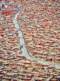 Un camino se divide un pueblo de cabañas de madera en dos partes en Serthar en el suroeste de la provincia de Sichuan. A la izquierda es donde viven las monjas, mientras que a la derecha están las casas de los monjes.